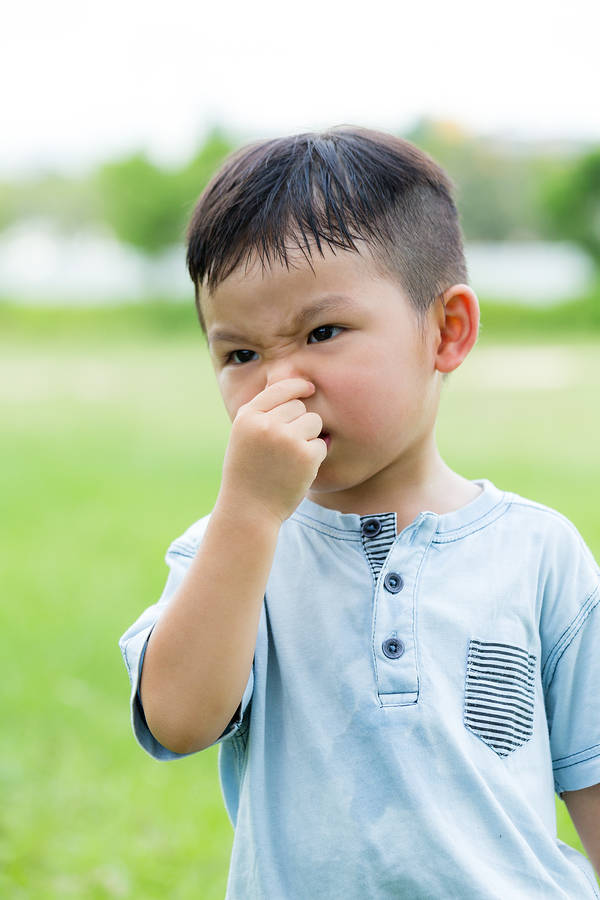 Little kid holding nose - read the Grossology books