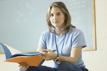 Female teacher sitting on desk