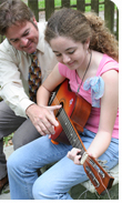 Father teaches daughter to play guitar
