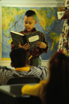 Boy reading to class with map