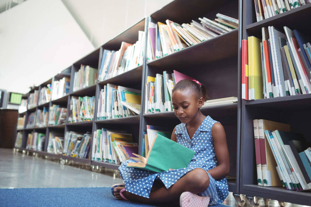 girl reading book in elementary school library