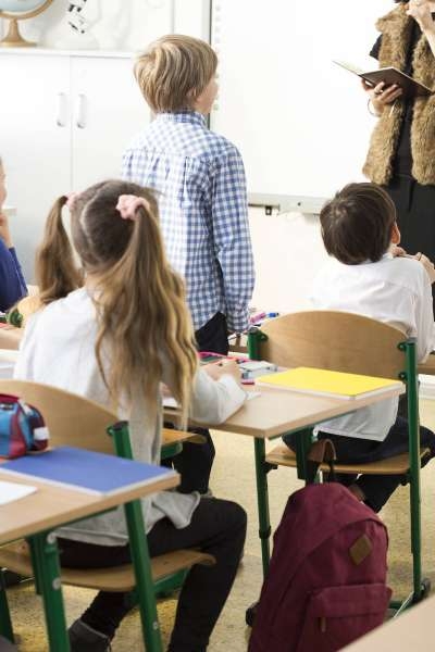 students looking toward a teacher in a classroom