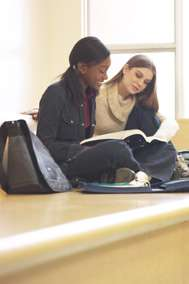 Teenage girls studying on bench